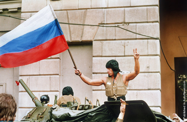 A soldier waves a Russian flag from the top of his tank as armored units leave their positions in Moscow following the collapse of the military coup against president Gorbachev on August 21, 1991. Coup leaders fled the capital and president Gorbachev was rumored to be returning soon