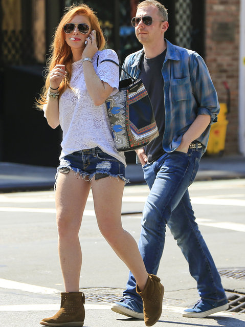 Actress Lindsay Lohan seen texting and smoking while accompanied by a male friend in Soho, New York City, on August 27, 2013. (Photo by PacificCoastNews.com)