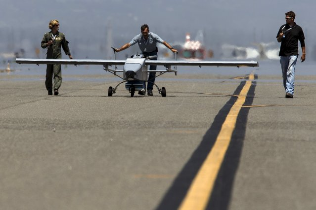 """The Navmar Applied Sciences Corp. TigerShark is escorted off the runway after landing during """"Black Dart"""", a live-fly, live fire demonstration of 55 unmanned aerial vehicles, or drones, at Naval Base Ventura County Sea Range, Point Mugu, near Oxnard, California July 31, 2015. (Photo by Patrick T. Fallon/Reuters)"""