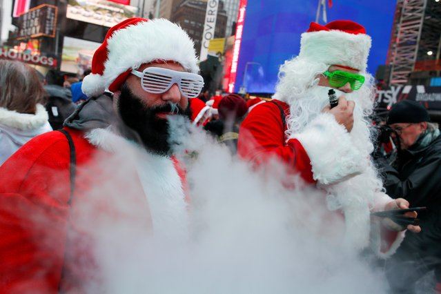 Revelers dressed as Santa Claus vape as they take part in the event called SantaCon at Times Square in New York City, U.S., December 14, 2019. (Photo by Eduardo Munoz/Reuters)