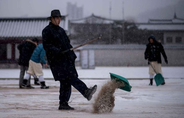 Workers clear snow from the grounds of Gyeongbokgung palace in central Seoul on January 13, 2017. (Photo by Ed Jones/AFP Photo)