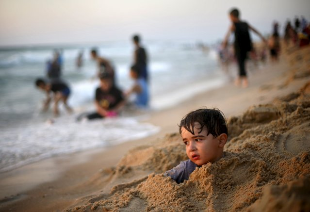 A Palestinian boy buries himself in the sand as he enjoys the warm weather with his family on a beach along the Mediterranean Sea in the northern Gaza Strip July 24, 2015. (Photo by Mohammed Salem/Reuters)