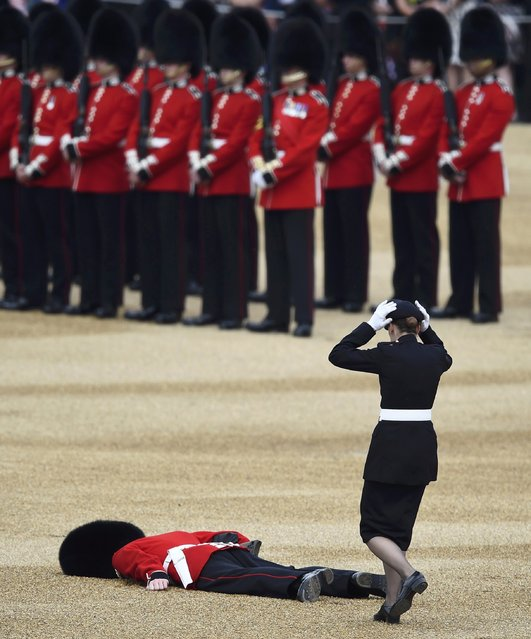 A Guardsman faints at Horseguards Parade for the annual Trooping the Colour ceremony in central London, Britain June 11, 2016. (Photo by Dylan Martinez/Reuters)