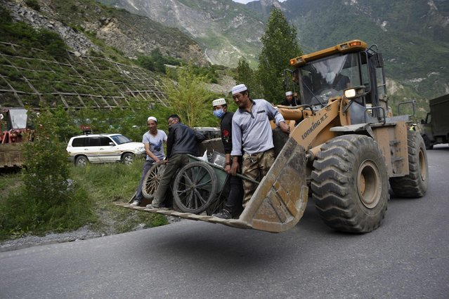 A group of Chinese Muslim stand on an excavator after bringing food to rescuers near a landslide area in the village of Xinmo in Maoxian county, China's Sichuan province on June 24, 2017. Rescuers dug through earth and rocks in an increasingly bleak search for more than 90 people still missing a day after their village in southwest China vanished under a huge landslide. (Photo by Wang Zhao/AFP Photo)