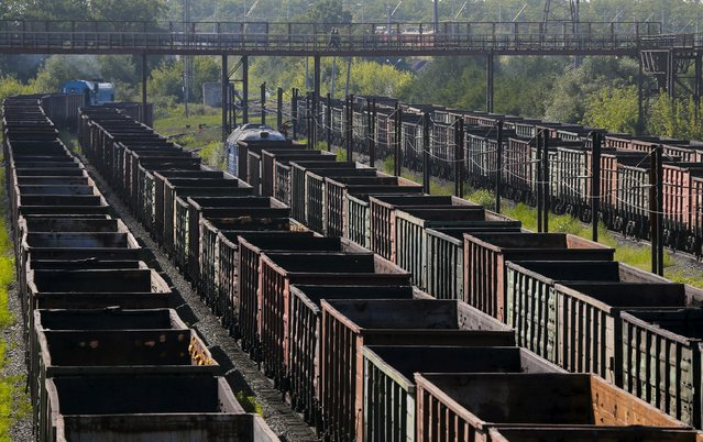Workers cross a bridge over cargo trains at the Stoilensky mining and concentration plant (GOK), owned by the Novolipetsk (NLMK) steel mill, in the city of Stary Oskol in Belgorod region, Russia, August 4, 2015. (Photo by Maxim Shemetov/Reuters)