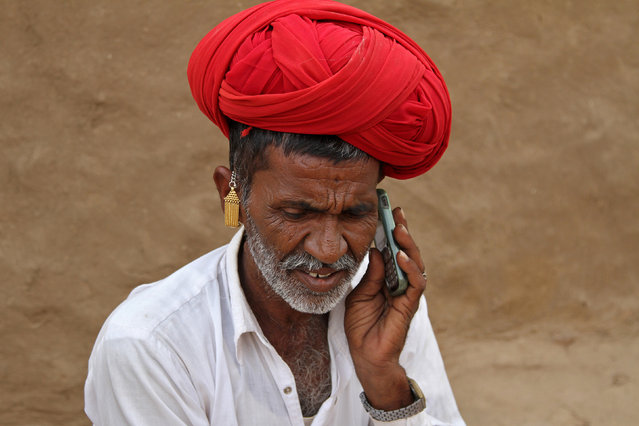 A man talks on his mobile phone in the village of Devmali in the desert state of Rajasthan, India June 14, 2016. (Photo by Himanshu Sharma/Reuters)
