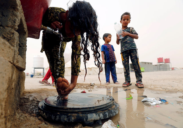 An Iraqi girl, who fled from Falluja because of Islamic State violence, wash at a refugee camp in Ameriyat Falluja, south of Falluja, Iraq, June 16, 2016. (Photo by Ahmed Saad/Reuters)