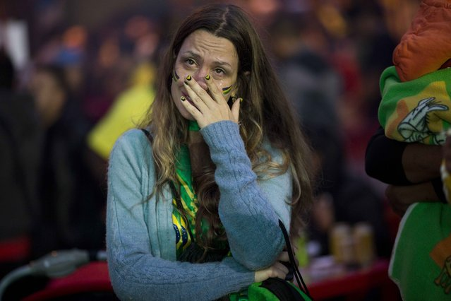 A Brazil soccer fan cries as she watches her team play Germany in a World Cup semifinal game via live telecast in Sao Paulo, Brazil, Tuesday, July 8, 2014. (Photo by Rodrigo Abd/AP Photo)