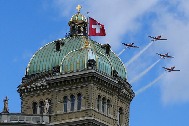 Four Pilatus PC-7 aircrafts of the Swiss Air Force fly over the Swiss Parliament building in Bern, Switzerland June 17, 2016. (Photo by Ruben Sprich/Reuters)