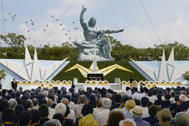 Doves fly over the Peace Statue in Nagasaki's Peace Park during a ceremony commemorating the 70th anniversary of the bombing of the city, in Nagasaki, western Japan, in this photo taken by Kyodo August 9, 2015. A bell tolled in Nagasaki on Sunday morning as the Japanese city marked 70 years since the dropping of the last atomic bomb on a civilian target in the closing days of World War Two. (Photo by Reuters/Kyodo News)