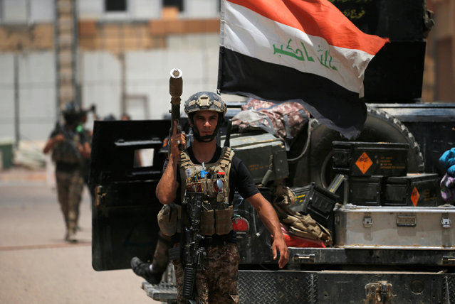 A member of the Iraqi security forces carries his weapon at Falluja hospital in center of Falluja, Iraq, June 20, 2016. (Photo by Thaier Al-Sudani/Reuters)