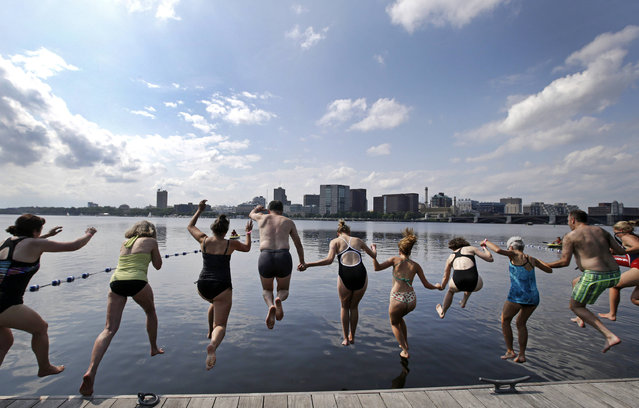 """People dive into the Charles River during the """"City Splash"""" event, Tuesday, July 18, 2017, in Boston. For the fifth year in a row, intrepid swimmers get a rare chance to beat the summer heat with a dip in the once notoriously filthy Charles River, where conservationists are working to build a permanent swim park. (Photo by Elise Amendola/AP Photo)"""