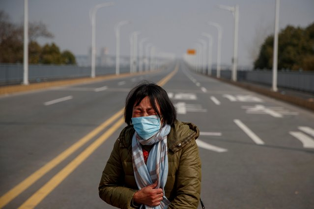 A mother reacts as she pleads with police to allow her daughter to pass a checkpoint for cancer treatment after she arrived from Hubei province at the Jiujiang Yangtze River Bridge in Jiujiang, China, February 1, 2020. (Photo by Thomas Peter/Reuters)