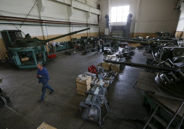 Employees work on turrets as armored vehicles are repaired at the Kiev armored plant, Ukraine, August 14, 2015. (Photo by Valentyn Ogirenko/Reuters)