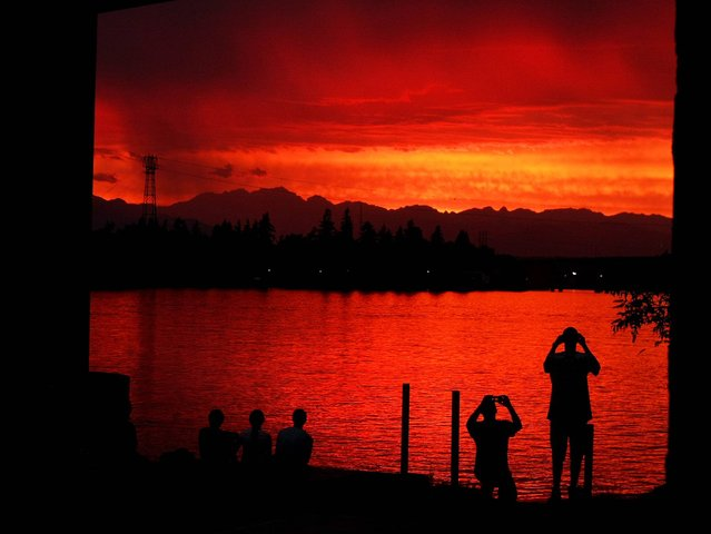 People watch the sunset under the Manette Bridge near the Boat Shed Restaurant in Bremerton, Wash., Sunday, July 13, 2014. (Photo by Larry Steagall/AP Photo/Kitsap Sun)