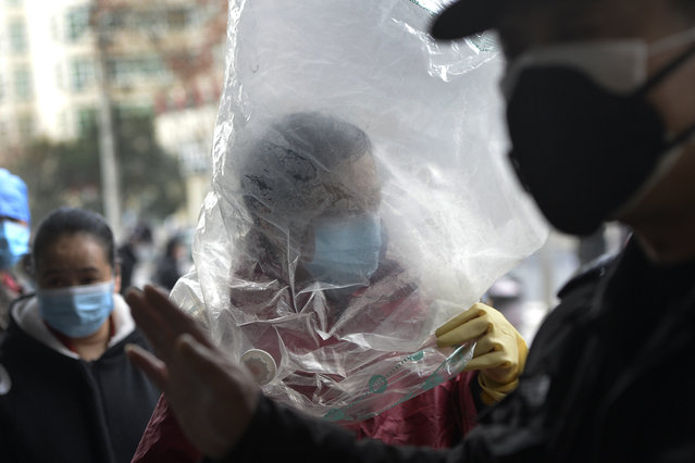 A man wearing a protective face mask covered himself with a plastic cover before enters a supermarket in Wuhan in central China's Hubei province, Monday, February 10, 2020. China reported a rise in new virus cases on Monday, possibly denting optimism that its disease control measures like isolating major cities might be working, while Japan reported dozens of new cases aboard a quarantined cruise ship. (Photo by Chinatopix via AP Photo)