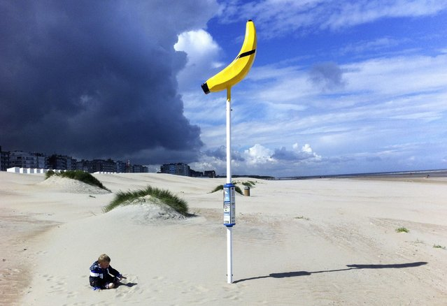 Three year-old boy Alessandro plays near a banana-shaped meeting point for lost children on the beach of Oostduinkerke July 11, 2012