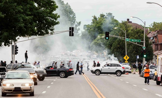 Smoke rises as police attempt to disperse protesters on Page  Ave. after a shooting incident in St. Louis, Missouri August 19, 2015. (Photo by Kenny Bahr/Reuters)