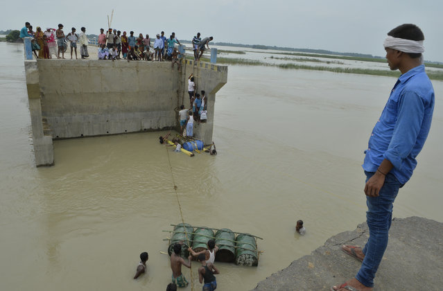 Indian villagers attempt to cross flood waters with the help of rope and empty canisters next to a washed away portion of a bridge at Palsa village in Purnia district in Bihar state on August 18, 2017. At least 221 people have died and more than 1.5 million have been displaced by monsoon flooding across India, Nepal and Bangladesh, officials said August 15, as rescuers scoured submerged villages for the missing. (Photo by Diptendu Dutta/AFP Photo)
