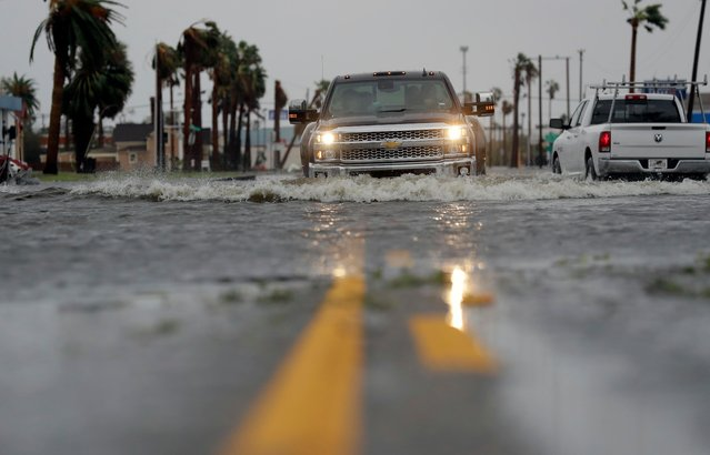 A drives moves through flood waters left behind by Hurricane Harvey, Saturday, August 26, 2017, in Aransas Pass, Texas. Harvey rolled over the Texas Gulf Coast on Saturday, smashing homes and businesses and lashing the shore with wind and rain so intense that drivers were forced off the road because they could not see in front of them. (Photo by Eric Gay/AP Photo)