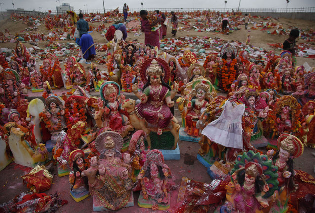 People collect idols of Hindu goddess Dashama left by devotees on the banks of the River Sabarmati at the end of Dashama festival in Ahmadabad, India, Monday, August 24, 2015. People collect these idols so that they can sell them next year ahead of the festival in other places. (Photo by Ajit Solanki/AP Photo)