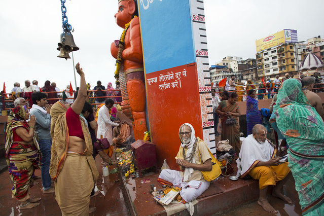 Hindu pilgrims offer prayers to an idol of monkey God Hanuman as they gather next to the Godavari River during Kumbh Mela, or Pitcher Festival, celebrations in Nasik, India, Wednesday, August 26, 2015. (Photo by Bernat Armangue/AP Photo)