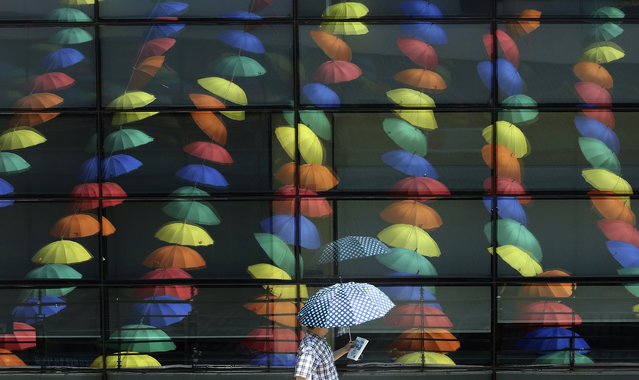 A man walks by window reflections of sun umbrellas used in an art display in a courtyard at the Geumcheon government building in Seoul, South Korea, Thursday, June 22, 2017. During past several days, the temperature soared over 30 degrees Celsius (86 degrees Fahrenheit), in afternoon, bringing a steamy heat to the capital area, according to weathermen. (Photo by Ahn Young-joon/AP Photo)