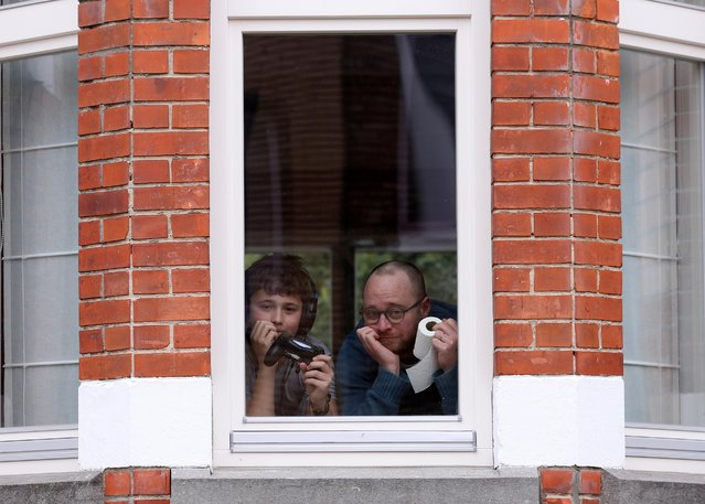 Resident Laurent Lanthier and his son Robin, 12, pose behind the window of their home with toilet paper and a game controller, objects significant to them during a coronavirus lockdown imposed by the Belgian government in an attempt to slow down the coronavirus outbreak in Brussels, Belgium on March 19, 2020. (Photo by Yves Herman/Reuters)