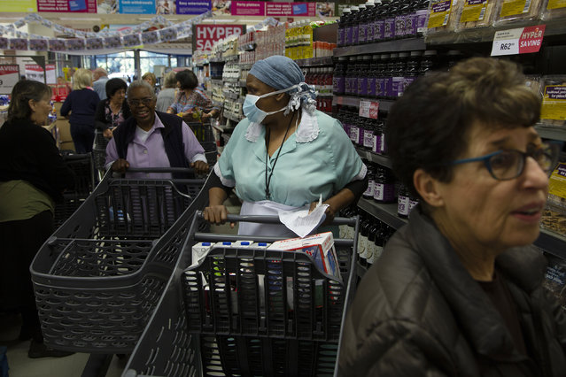 Shoppers make their way through a supermarket in Johannesburg, Wednesday, March 25, 2020 before the country of 57 million people, will go into a nationwide lockdown for 21 days from Thursday to fight the spread of the new coronavirus. (Photo by Denis Farrell/AP Photo)