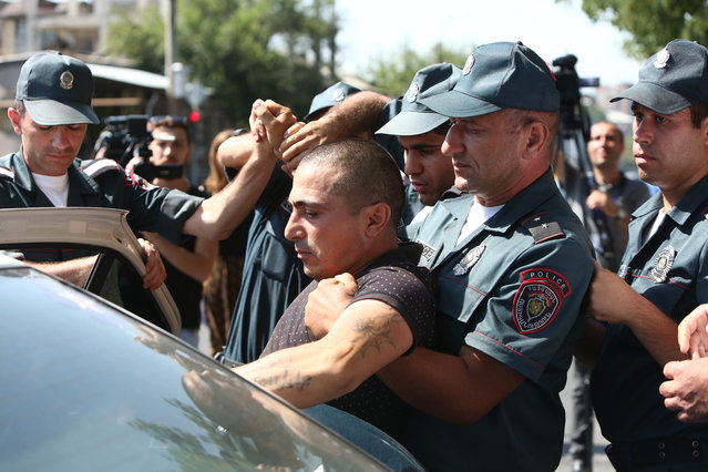 Armenian police detain an unidentified man in Yerevan, Armenia, Sunday, June 17, 2016. Armed supporters of a jailed opposition leader attacked a police station in Armenia's capital on Sunday, killing one officer, wounding two and taking several others hostage, the National Security Service said.The attackers demanded the release of Jirair Sefilian, who was arrested last month, and called for the ouster of the government. (Photo by Hrant Khachatryan/PAN Photo via AP Photo)