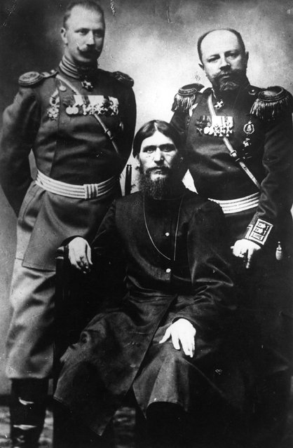 Russian peasant and mystic Grigory Yefimovich Rasputin (1869–1916), centre, former peasant and self-styled holy man, sitting between two military men in uniform, 1910.