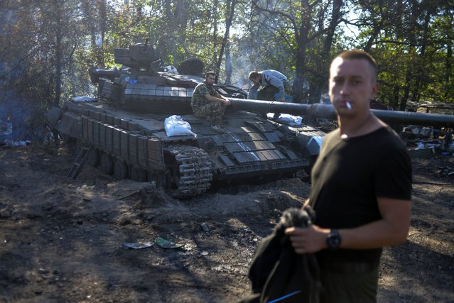 Ukrainian soldiers stand by a tank near the eastern Ukrainian city of Luhansk, on August 21, 2014. A Ukrainian warplane was blown out of the sky over rebel-held territory as fierce clashes between government troops and pro-Russian insurgents left dozens of civilians dead. (Photo by Aleksey Chernyshev/AFP Photo)