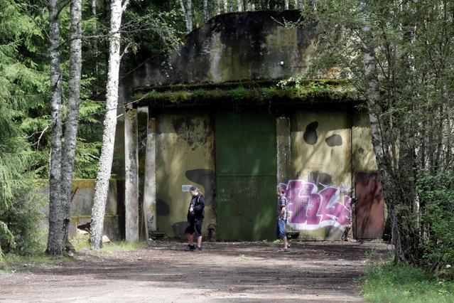 People walk past abandoned former Soviet R12 nuclear missile hangar in Zeltini, Latvia, July 22, 2016. (Photo by Ints Kalnins/Reuters)