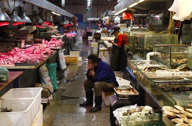 A Chinese vendor takes a rest amid stalls of meat and seafood at a public market in Beijing, China, 11 September 2015. Consumer inflation in China reached its highest point for a year as consumer price index was up 2 per cent year-on-year in August, while the producer price index was down 5.9 per cent and indicated the biggest drop in more than five years, the National Bureau of Statistics (NBS) said on 10 September. (Photo by Rolex Dela Pena/EPA/EFE)