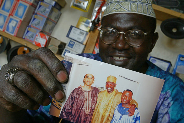 This Tuesday, September 14, 2004 file photo shows Malik Obama, the older brother of US President Barack Obama, who holds an undated picture of Barack, left, and himself, center, and an unidentified friend in his shop in Siaya, eastern Kenya. A Kenyan half-brother of President Barack Obama says he will vote for Republican presidential nominee Donald Trump and not the candidate his brother has endorsed, Hillary Clinton. Malik Obama told The Associated Press on Tuesday that he thinks Trump has a lot of energy and is very straightforward. (Photo by Karel Prinsloo/AP Photo)