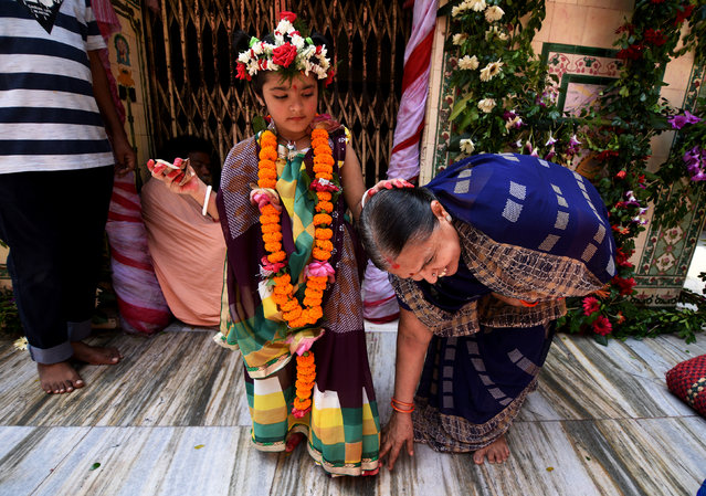 A Hindu devotee takes blessings of a girl dressed as Kumari, who is worshipped during the Durga Puja festival, at Kamakhya temple in Guwahati, India September 22, 2017. (Photo by Anuwar Hazarika/Reuters)