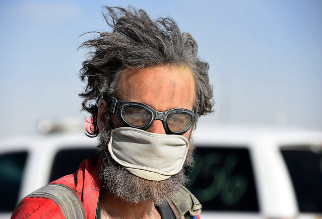 An unidentified man walks southbound on 6:30 Street on Wednesday, September 2, 2015, on the Black Rock Desert of Nevada. Burners have another day of dust on the playa at Burning Man. (Photo by Andy Barron/The Reno Gazette-Journal via AP Photo)