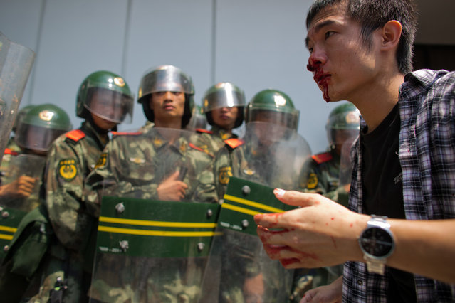 An anti-Japanese protester bleeds from the nose as riot police look on, during a demonstration over the disputed Diaoyu/Senkaku Islands, on September 16, 2012 in Shenzhen, China. (Photo by Lam Yik Fei)