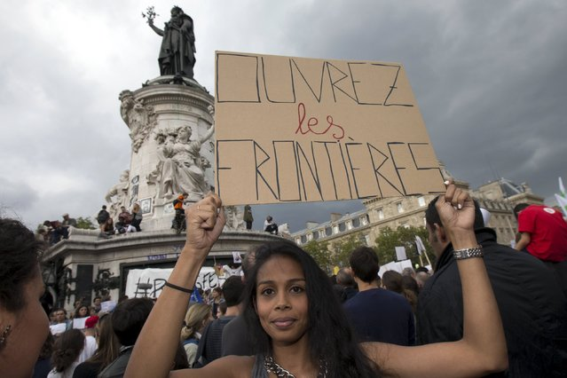 """A woman holds a sign that says """"Open the borders"""" during a demonstration asking for a change in the refugee policy in Europe on the Republique square in Paris, France, September 5, 2015. (Photo by Philippe Wojazer/Reuters)"""