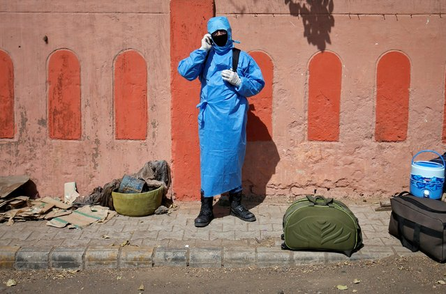 A man wearing protective gear speaks on his mobile phone as he waits for transport upon his arrival from New Delhi outside a railway station, after a limited reopening of India's giant rail network following a nearly seven-week lockdown to slow the spreading of the coronavirus disease (COVID-19), in Ahmedabad, India, May 14, 2020. (Photo by Amit Dave/Reuters)