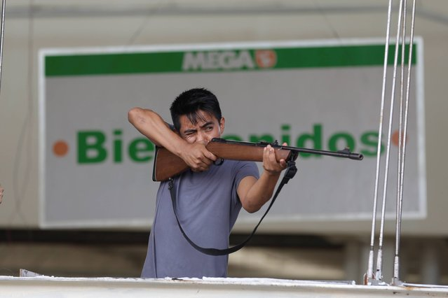 """An employee from Mega Supermarket fires an air rifle at people trying to loot the store in Los Cabos, Mexico, Tuesday, September 16, 2014. The sign in the background reads in Spanish """"Welcome"""". According to employees the supermarket donated all the food in the store and established a system by which every person had 5 minutes to get whatever they could for free. (Photo by Victor R. Caivano/AP Photo)"""