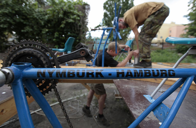 Jakub Bures (L) and Jan Holan attach a plastic garden chair to a wooden frame as they build a boat in their yard in Nymburk July 1, 2014. (Photo by David W. Cerny/Reuters)