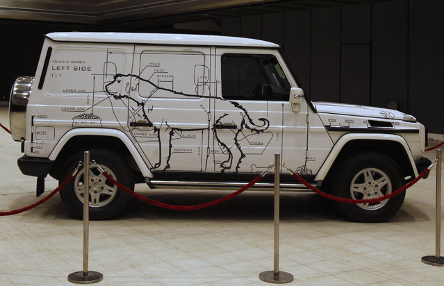 """An artwork by Chinese artist Ai Weiwei, titled """"The Dog Mobile: A car for Francis Bacon by Ai Weiwei"""", with images of a dog painted on a Mercedes Benz G-class, is displayed at an exhibition hall in Hong Kong November 29, 2011. (Photo by Bobby Yip/Reuters)"""