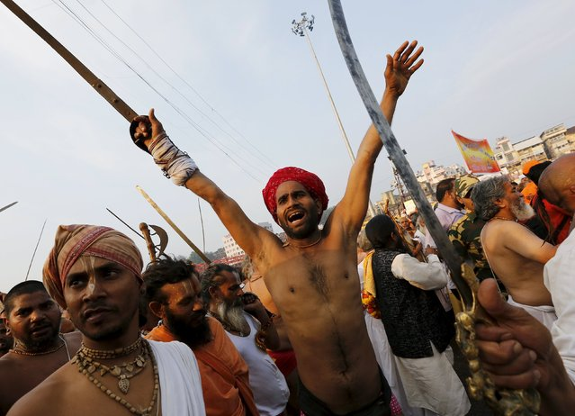 "Sadhus or Hindu holy men shout religious hymns as they arrive to take a dip in the waters of Godavari river during the second ""Shahi Snan"" (grand bath) at Kumbh Mela or Pitcher Festival in Nashik, India, September 13, 2015. Hundreds of thousands of Hindus took part in the religious gathering at the banks of the Godavari river in Nashik city at the festival, which is held every 12 years in different Indian cities. (Photo by Adnan Abidi/Reuters)"