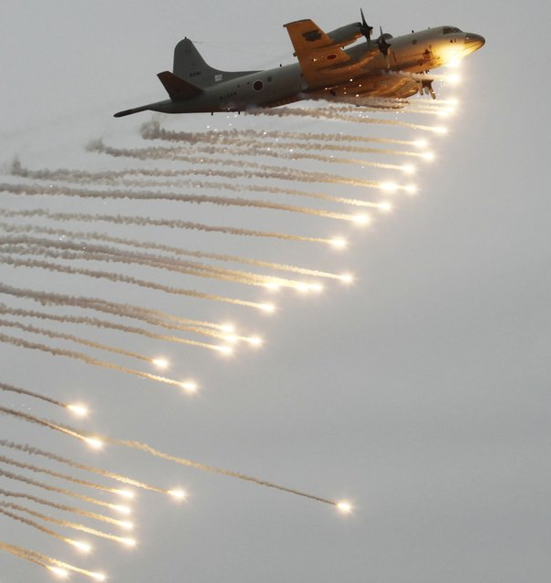A Japanese Maritime Self-Defense Force (JMSDF) P3C anti-submarine patrol plane fires flares during a fleet review in Sagami Bay, south of Tokyo, Japan, Sunday, Oct. 14, 2012. Japan's navy marked its 60th anniversary with a major exercise intended to show off its maritime strength. The display comes amid a tense territorial dispute with China. (Photo by Yuriko Nakao/Reuters)
