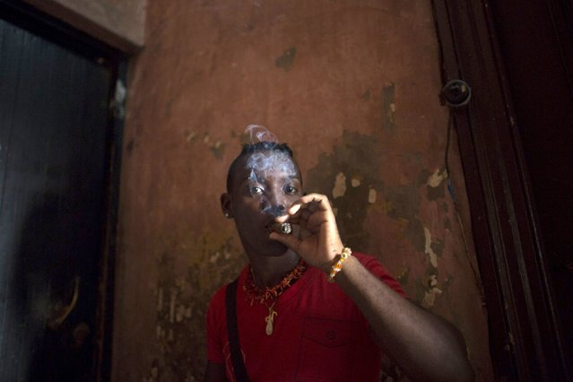Santeria practitioner Yuris Landis, a 27-year-old nurse, smokes a cigar during a ceremony of the Afro-Cuban religion Santeria to attract spirits of dead ancestors to ask for guidance in downtown Havana, August 18, 2015. (Photo by Alexandre Meneghini/Reuters)