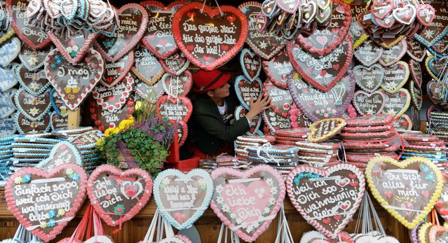 A vendor prepares a booth with gingerbread hearts during the Oktoberfest festival fair ground at the Theresienwiese in Munich, southern Germany, on October 1, 2014. Germany's world-famous Oktoberfest takes place until October 5, 2014. (Photo by Christof Stache/AFP Photo)