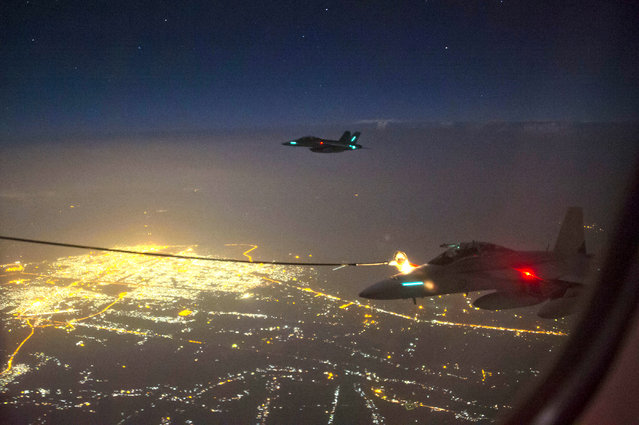 """A handout photo taken October 5, 2014 and obtained on October 9 shows two Royal Australian Air Force (RAAF) F/A-18F Super Hornet aircraft refuelling from a RAAF KC-30A Multi Role Tanker Transport aircraft above a city in Iraq.  A Super Hornet fighter jet has carried out Australia's first bombing raid in Iraq, targeting what the defence ministry on October 9, 2014, described as a """"facility"""" of the Islamist State group. (Photo by Hamish Paterson/AFP Photo/Australian Defence)"""