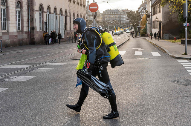 A diver crosses a street after taking part in a cleanup mission of the Ill river in Strasbourg, eastern France, on November 18, 2017. Hundreds of citizens and some divers gathered to pick up trash from the banks and inside the river. (Photo by Patrick Hertzog/AFP Photo)