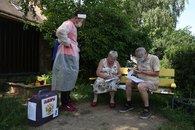 Local residents fill in documents as a member of an electoral commission stands nearby with a mobile ballot box during a seven-day vote on constitutional reforms, in the village of Troitskoye in Moscow region, Russia on June 25, 2020. (Photo by Evgenia Novozhenina/Reuters)